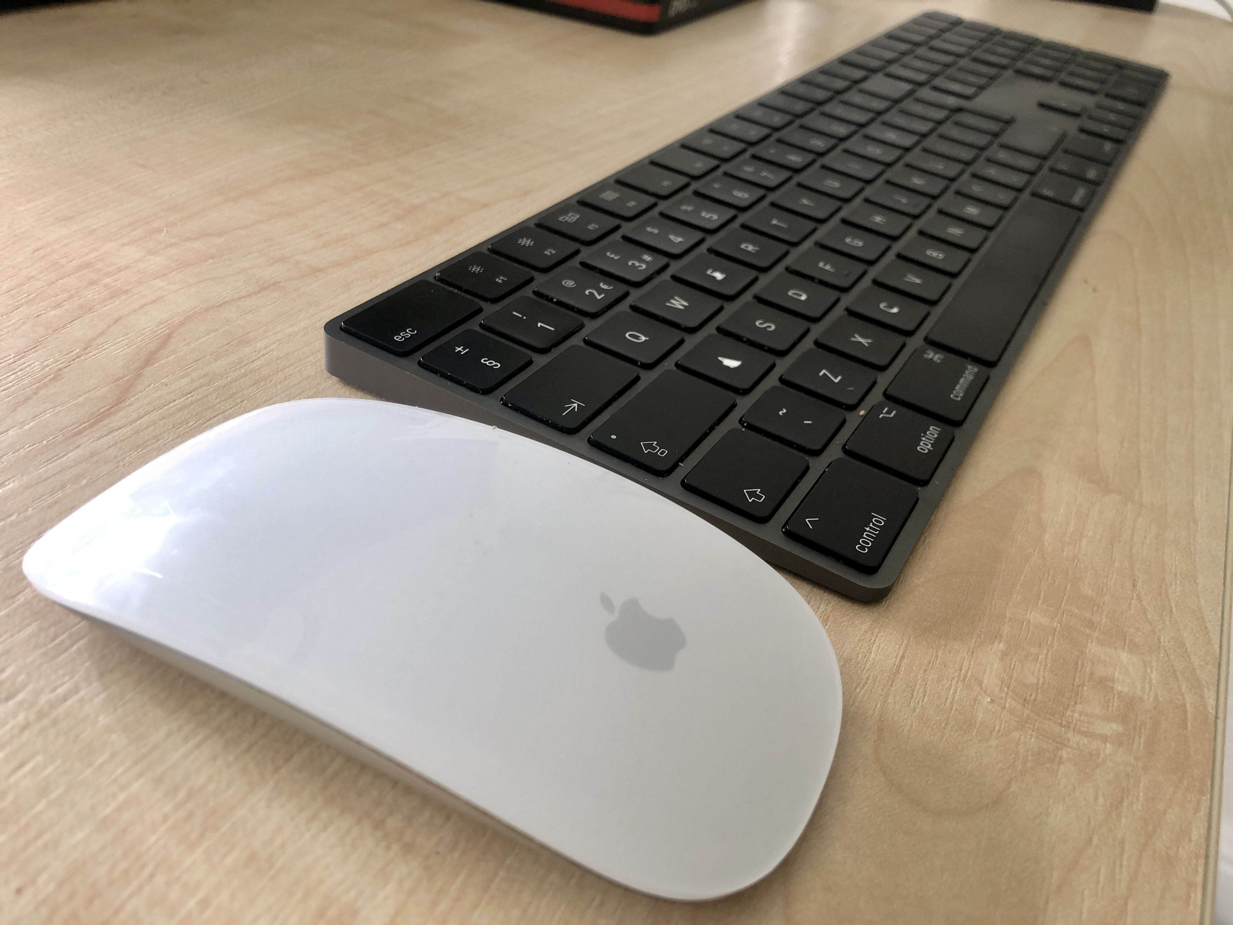 Photo of a white Apple Magic Mouse next to a black Apple keyboard, on a desk